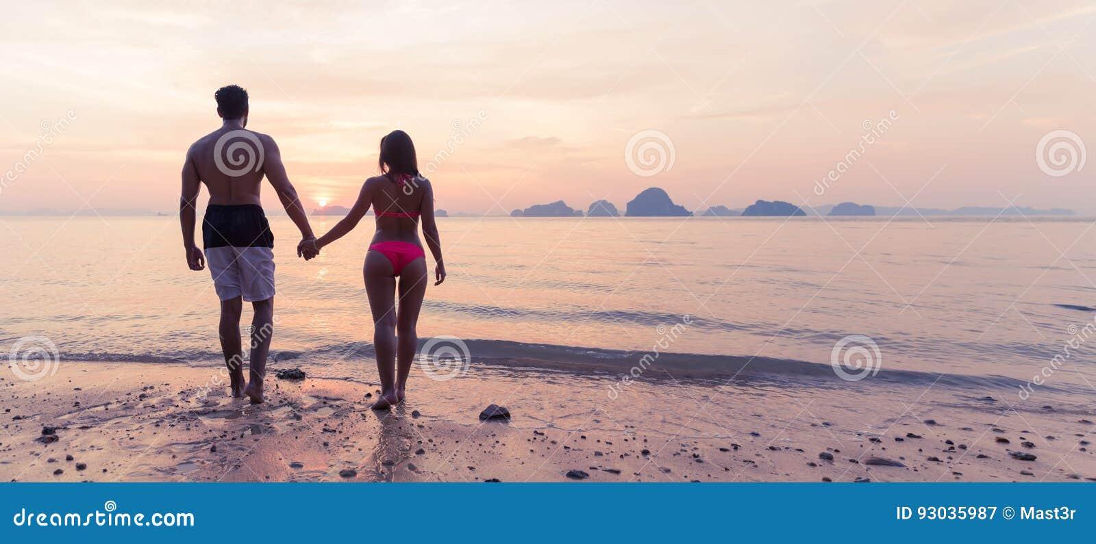 ad2a34d64 Pares que guardam as mãos na praia na opinião traseira da parte traseira do  por do sol, no homem novo do turista e na mulher no feriado do mar quando  férias ...