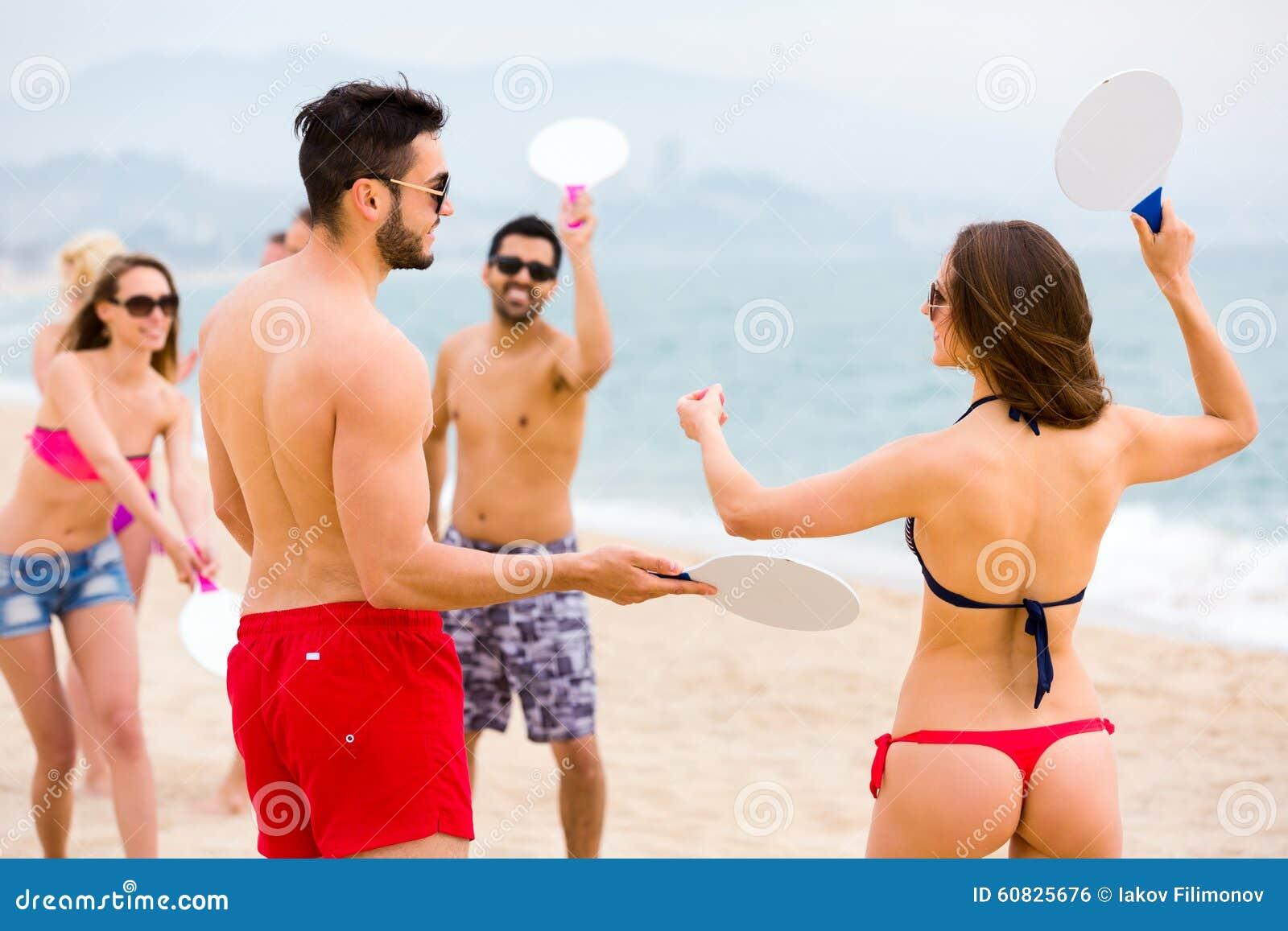 Pares que juegan a juegos en una playa