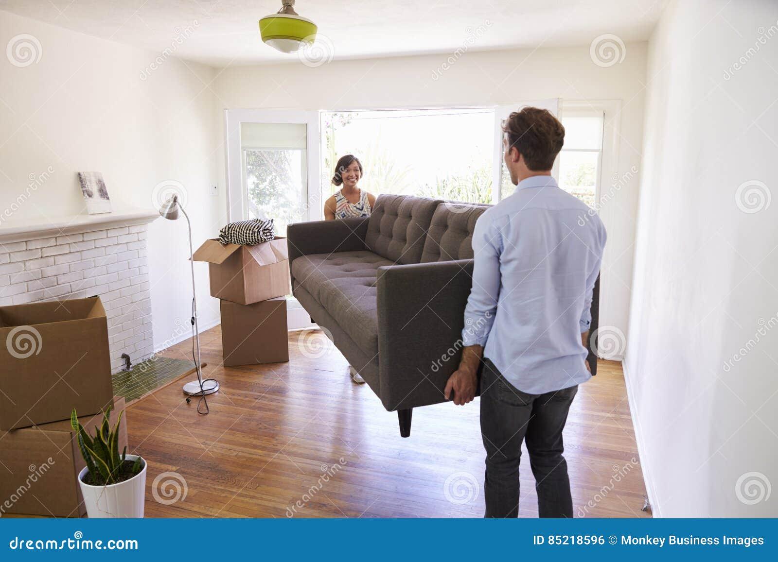 Pares que levam dia movente de Sofa Into New Home On