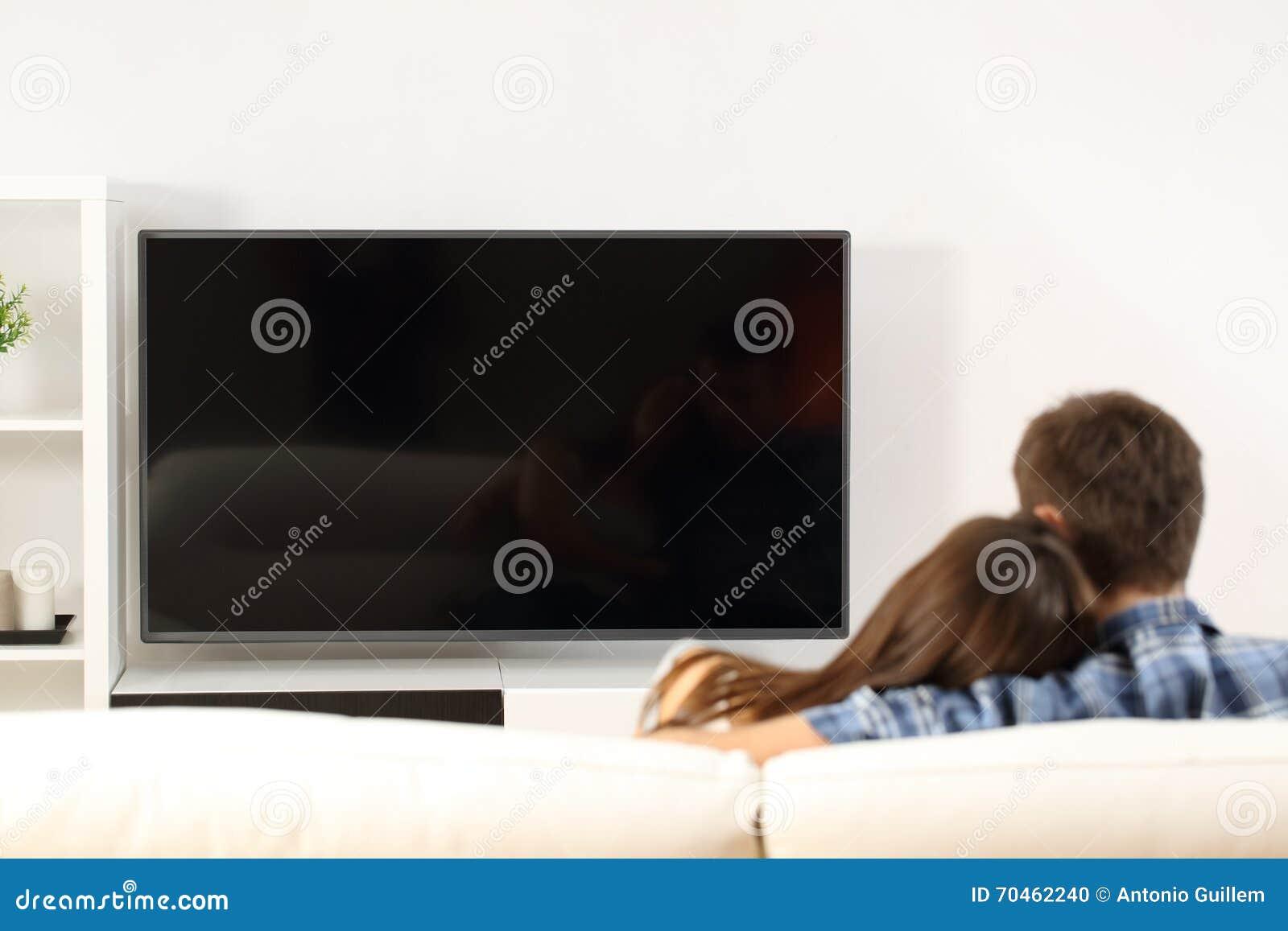 Pares que miran la opinión de la pantalla de la TV