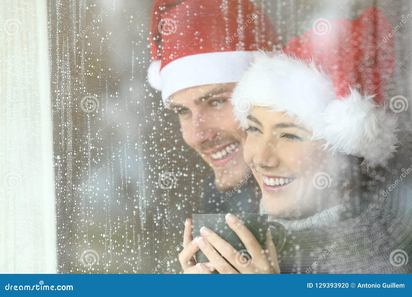 Pares que olham através de uma janela no Natal