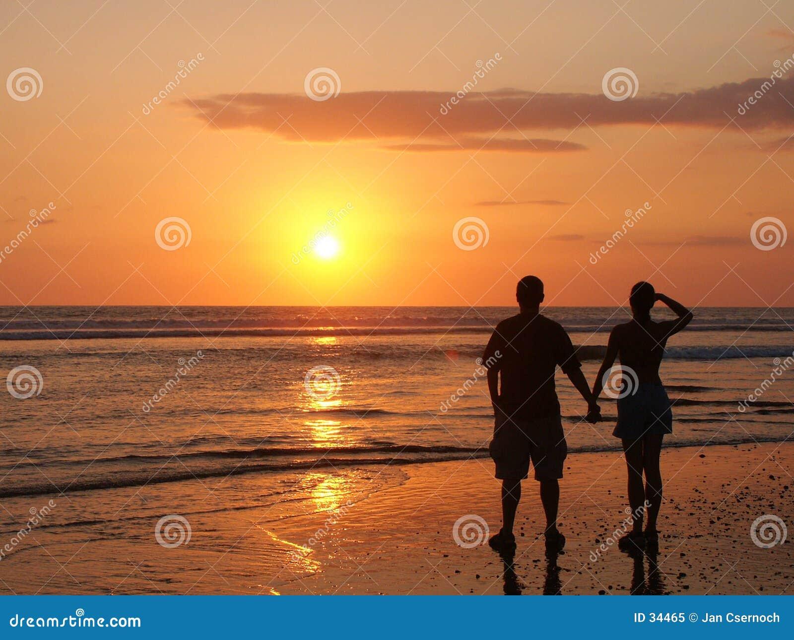Pares que prestam atenção ao sol de ajuste em conjunto