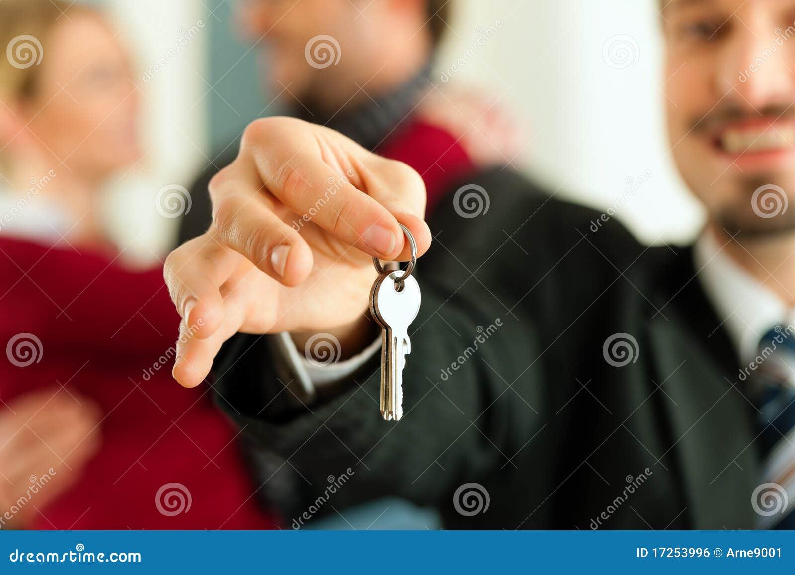 Pares que recebem chaves do corretor de bens imobiliários
