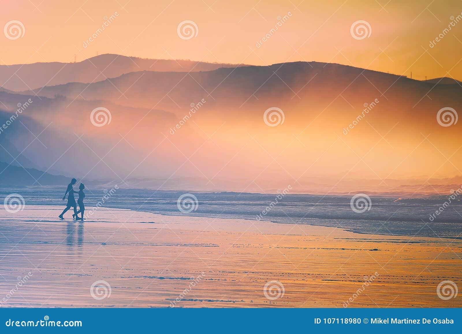 Download Pares Que Recorren En La Playa En La Puesta Del Sol Foto de archivo - Imagen de ocio, persona: 107118980