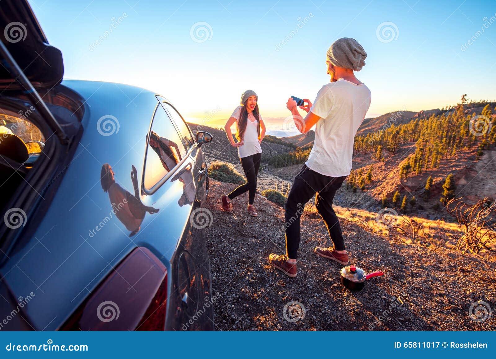 Pares que se divierten cerca del coche