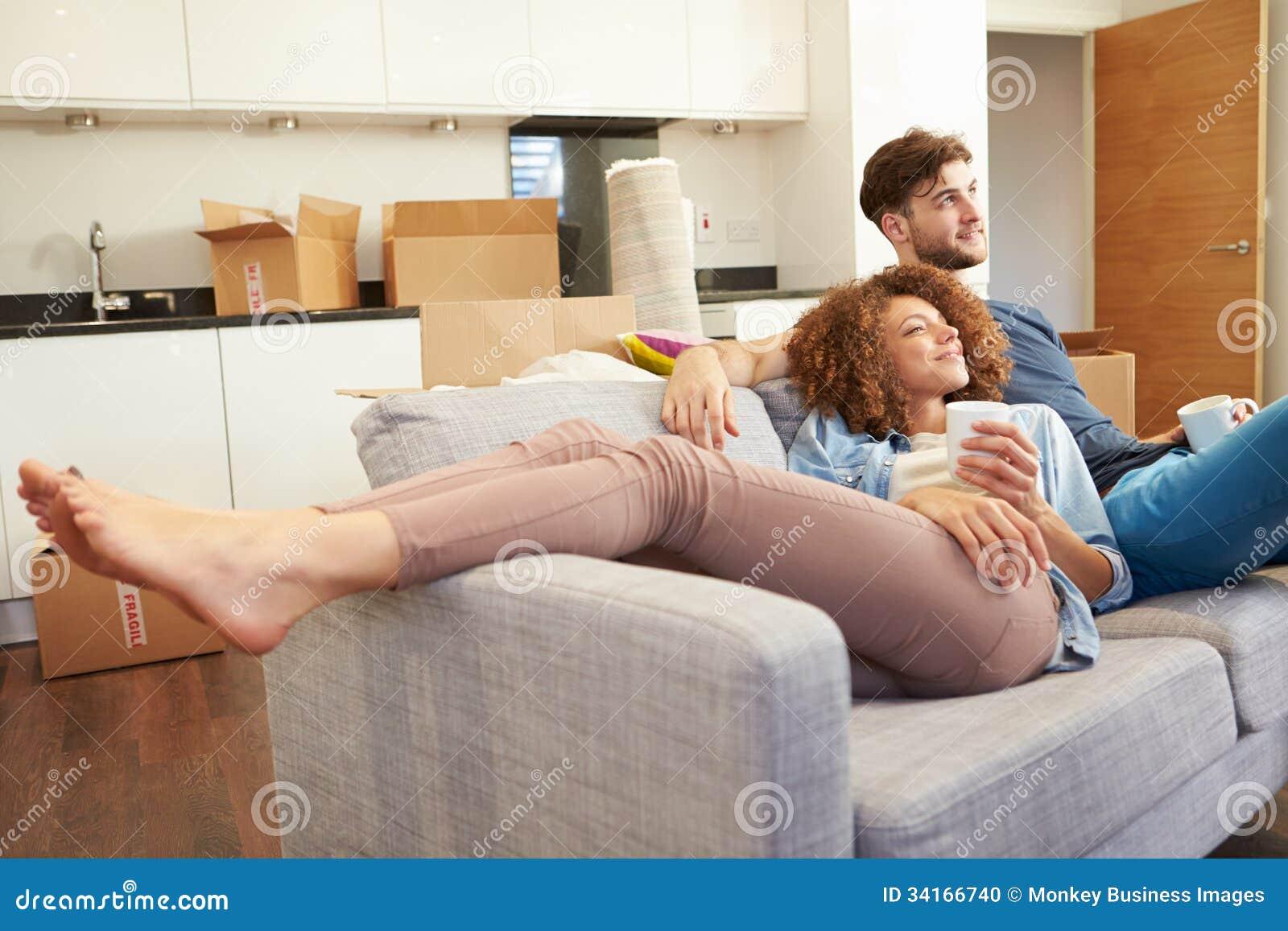 Pares que se relajan en el nuevo hogar de Sofa With Hot Drink In