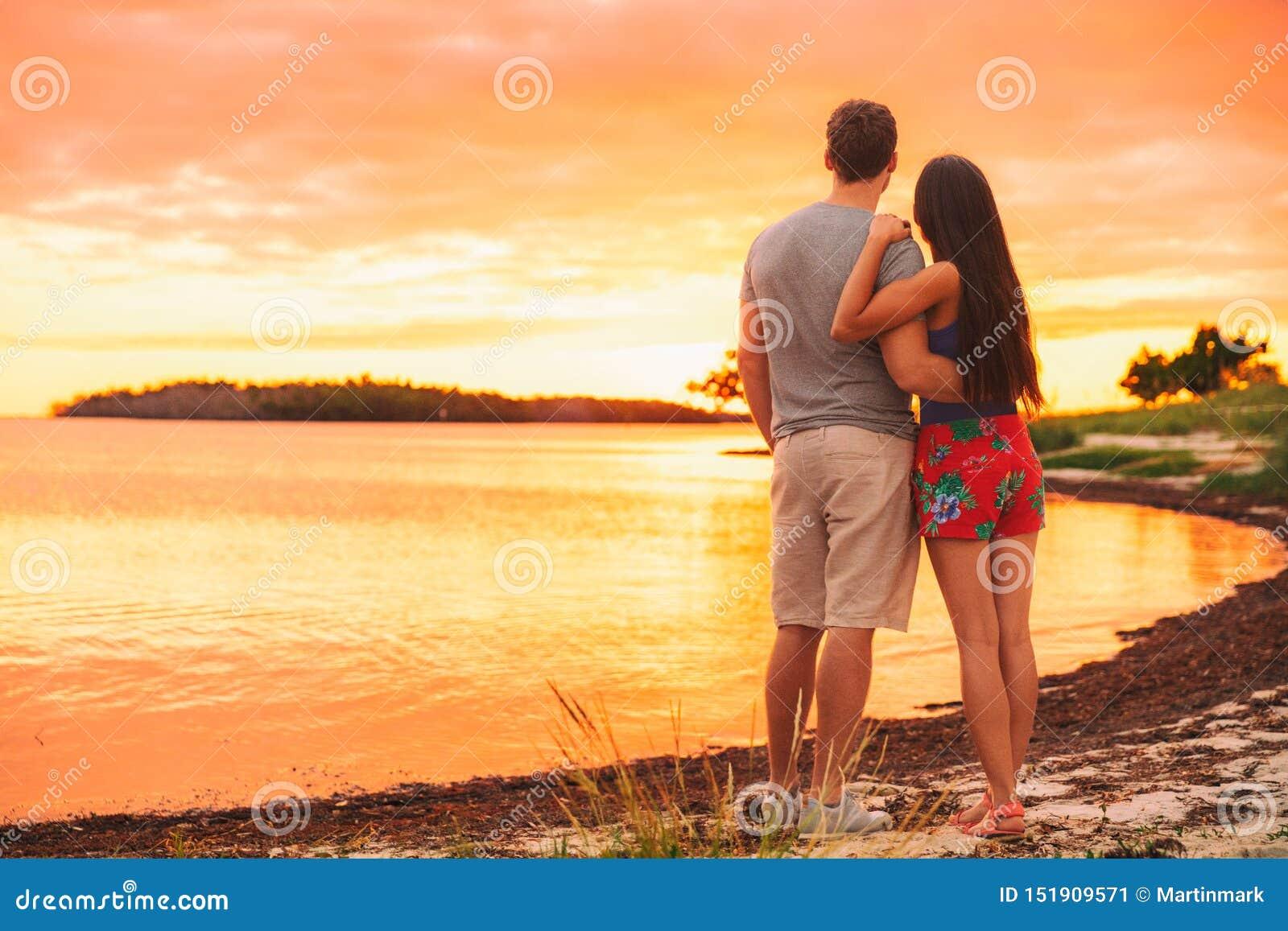 Pares que se relajan en la situación del viaje de las vacaciones de verano en puesta del sol de observación de la playa en el des