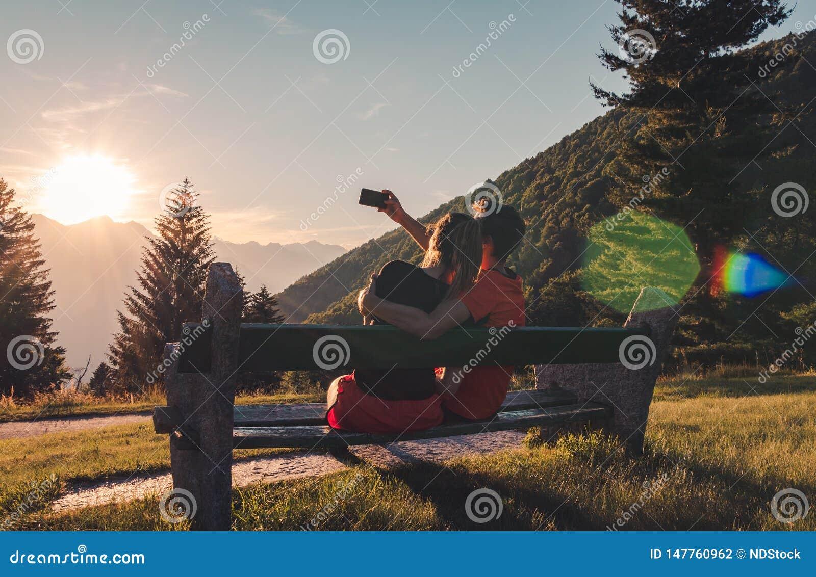 Pares que se sientan en banco en las montañas que miran la puesta del sol y que toman un selfie