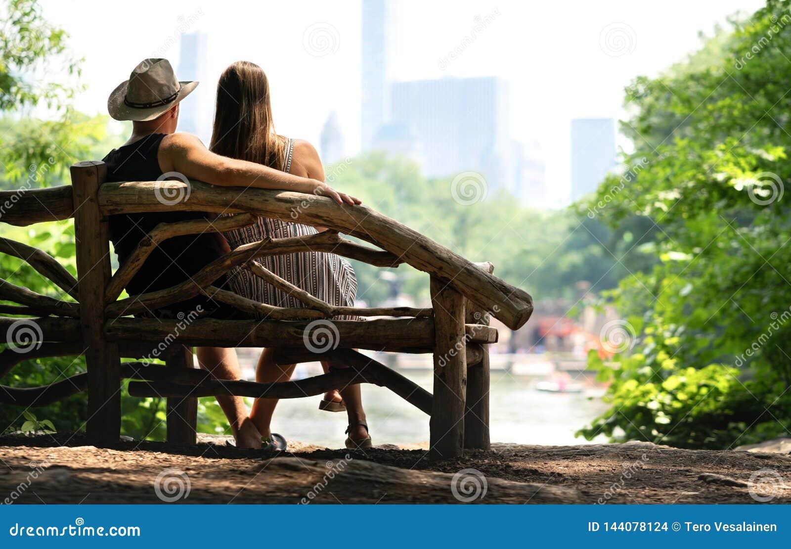 Pares que se sientan en un banco de parque y que tienen una primera fecha romántica Amantes con romance y confianza