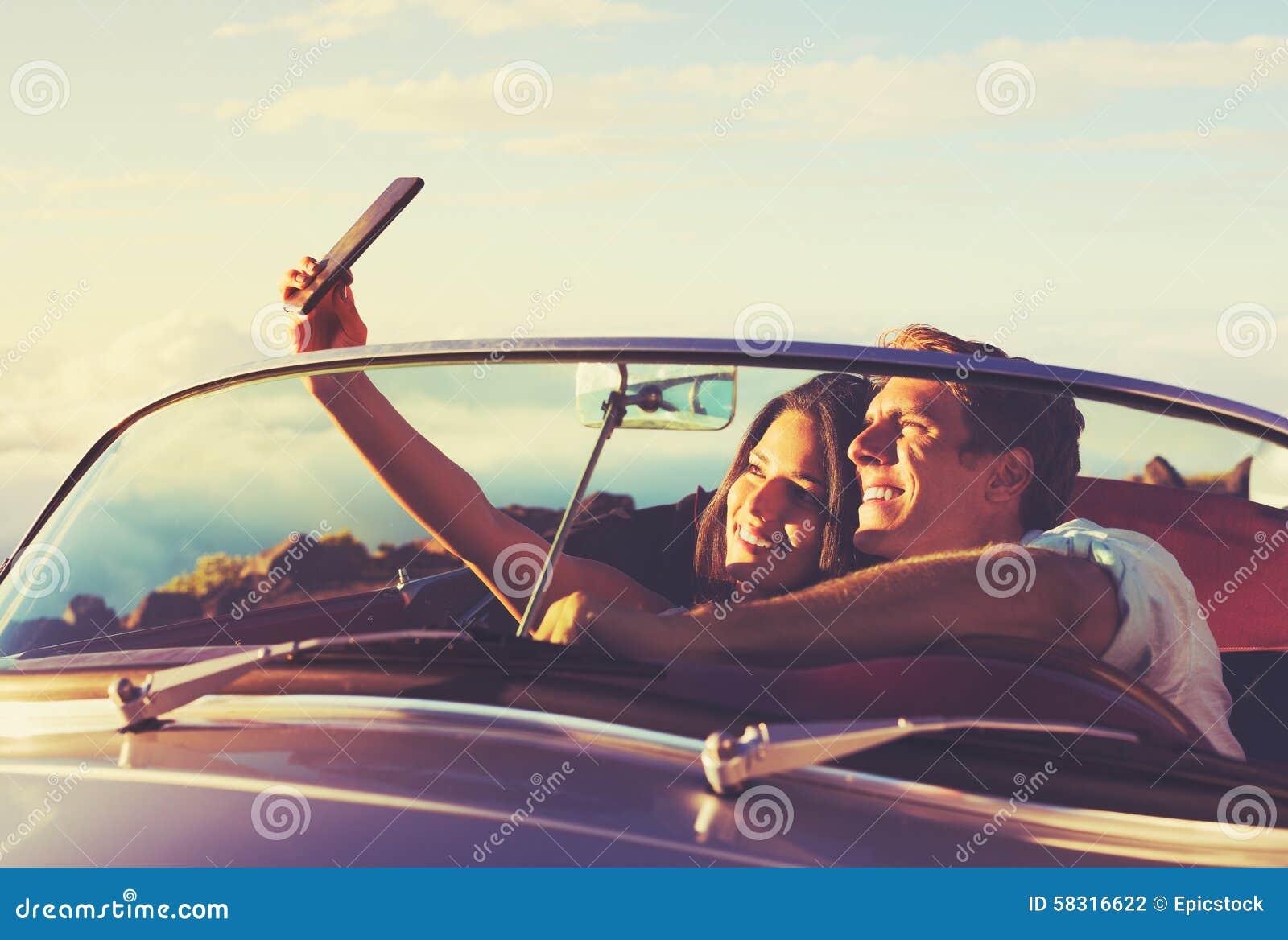 Pares que tomam um Selfie no carro no por do sol