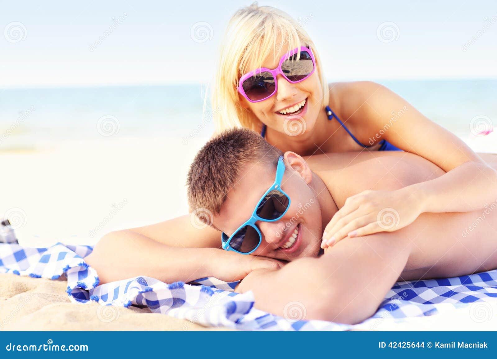 Pares que toman el sol en la playa