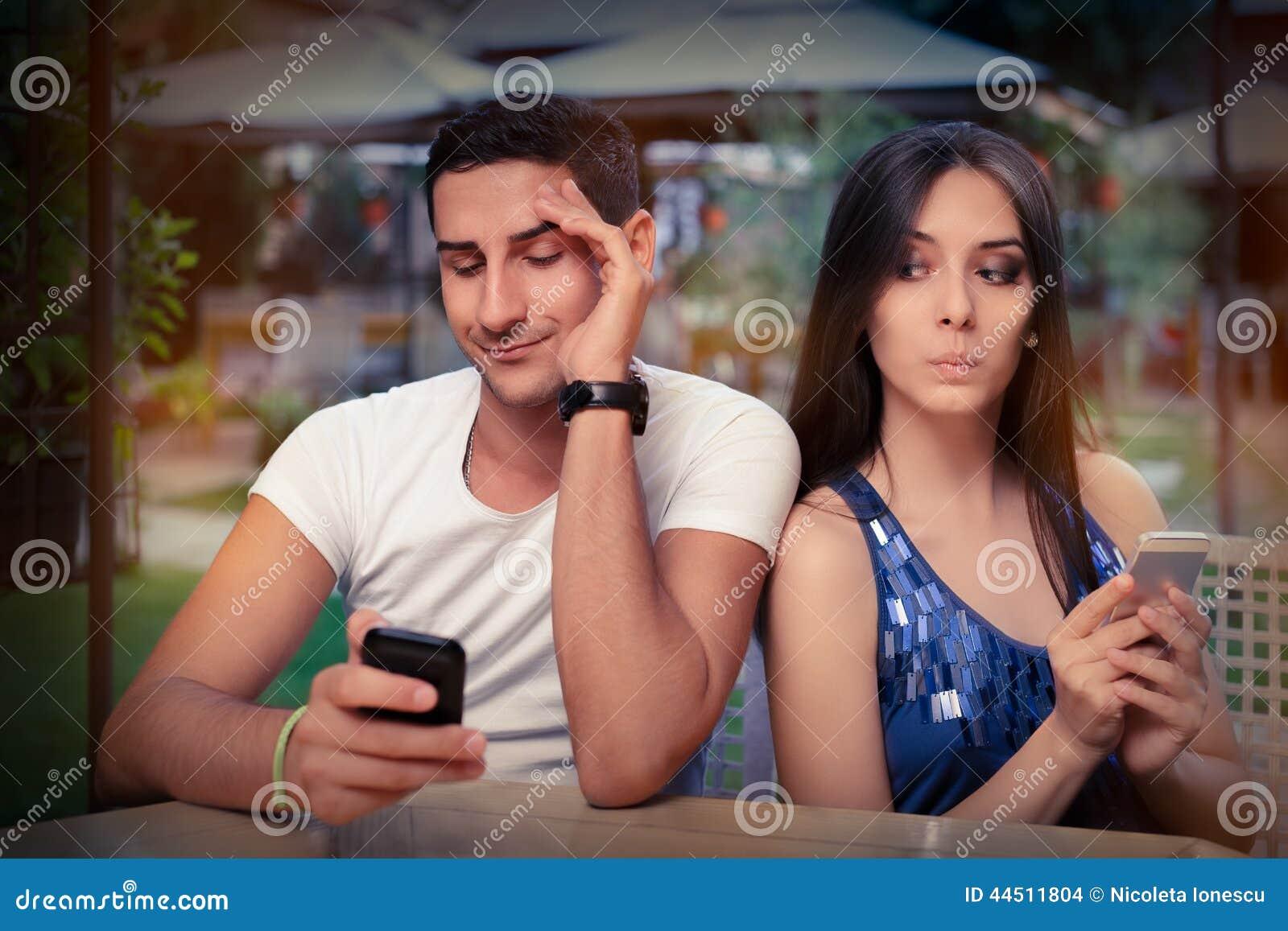 Pares reservados con los teléfonos elegantes en sus manos