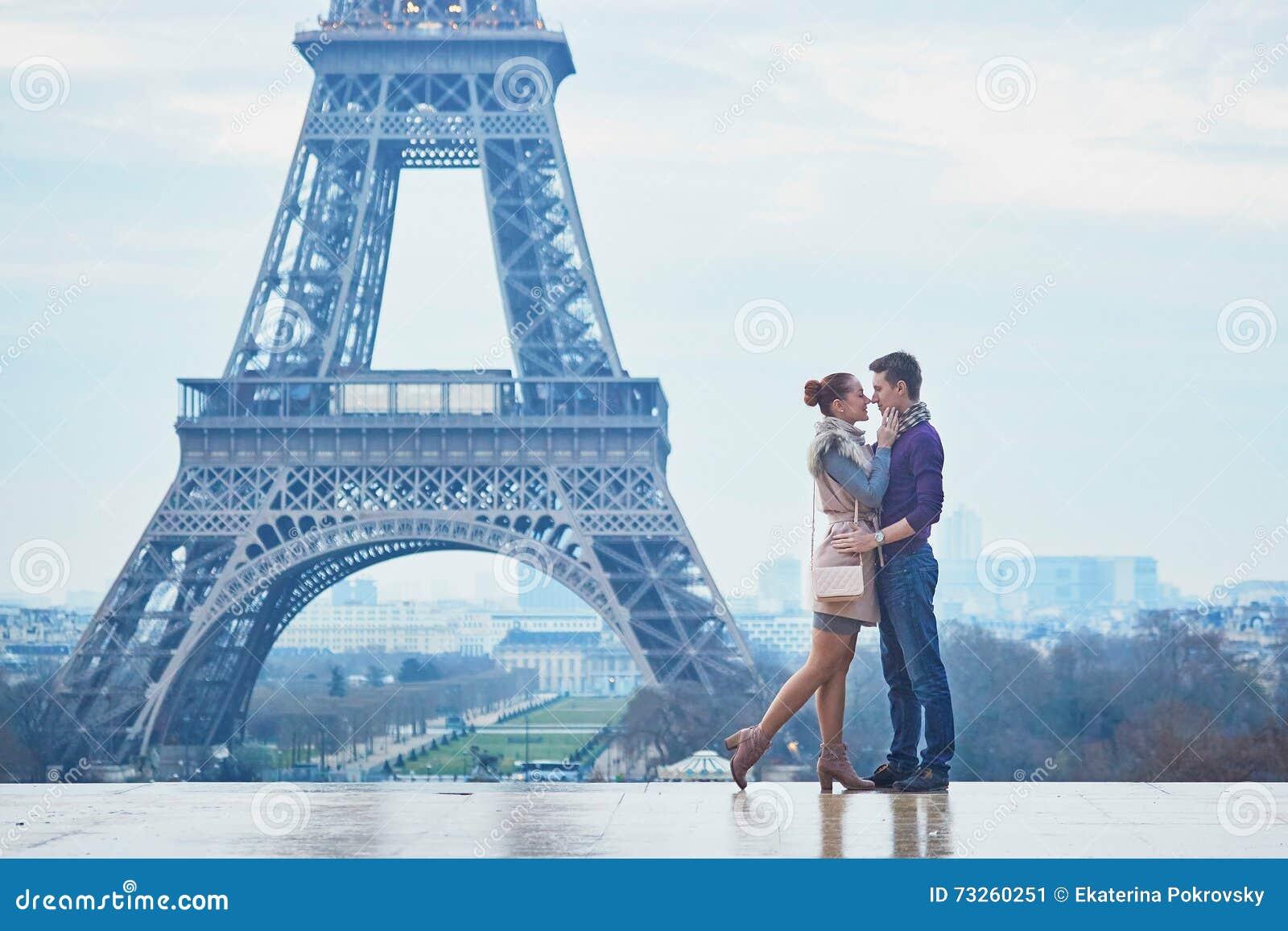 Pares románticos cerca de la torre Eiffel en París, Francia