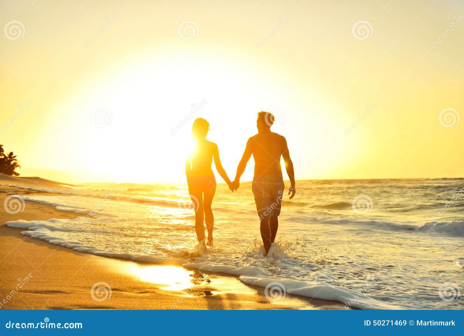 Pares románticos de la luna de miel en amor en la puesta del sol de la playa