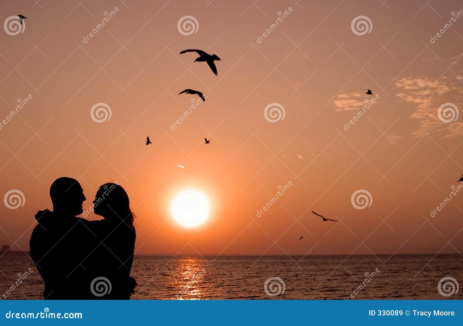 Pares románticos en la puesta del sol