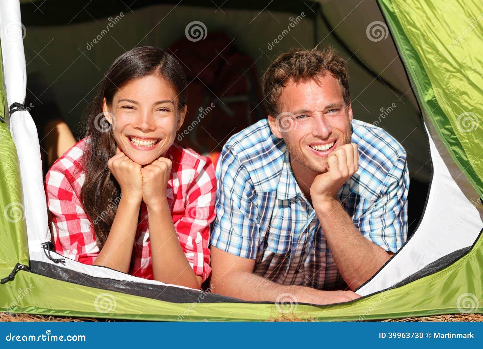 Pares románticos felices que acampan en la mirada de la tienda