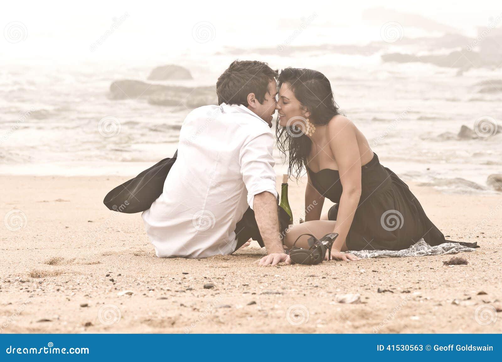 Pares románticos jovenes que se besan en la playa