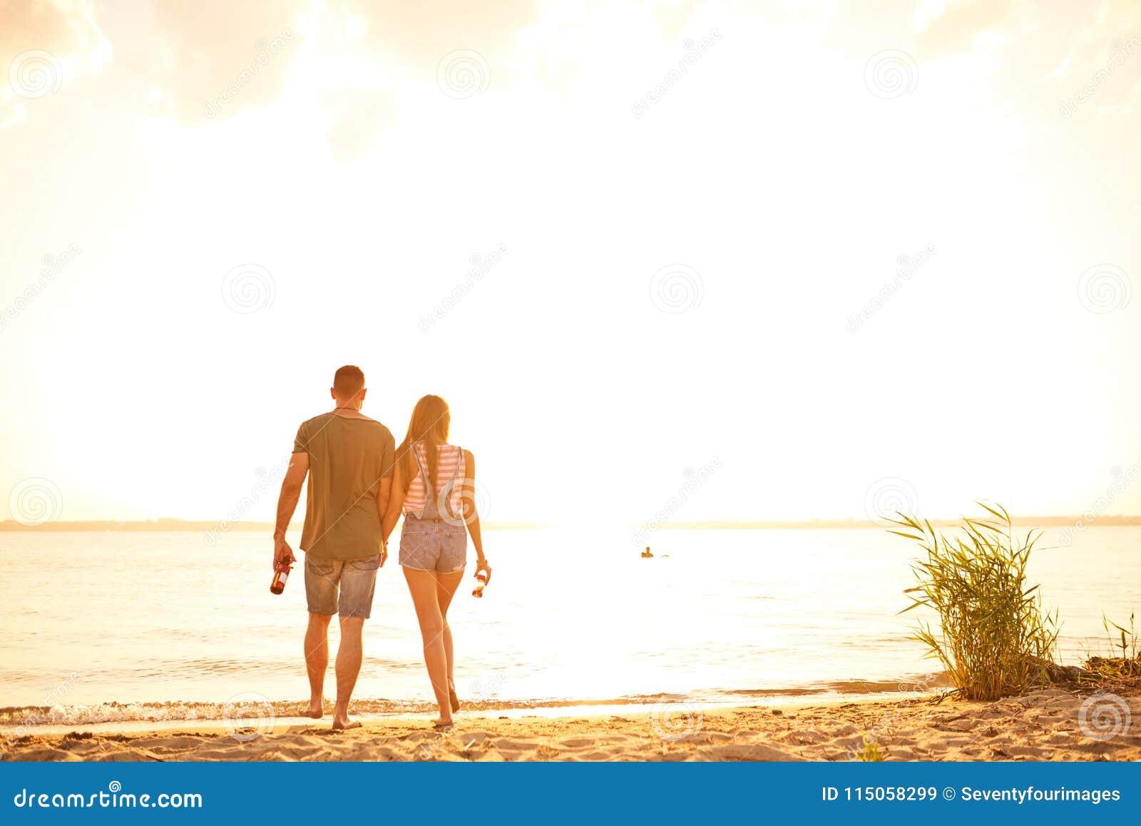 Pares románticos que caminan sobre la playa durante fecha