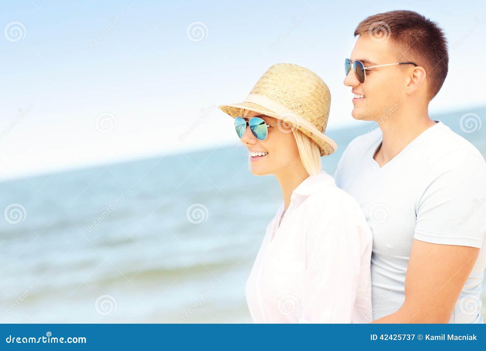 Pares románticos que se colocan en la playa