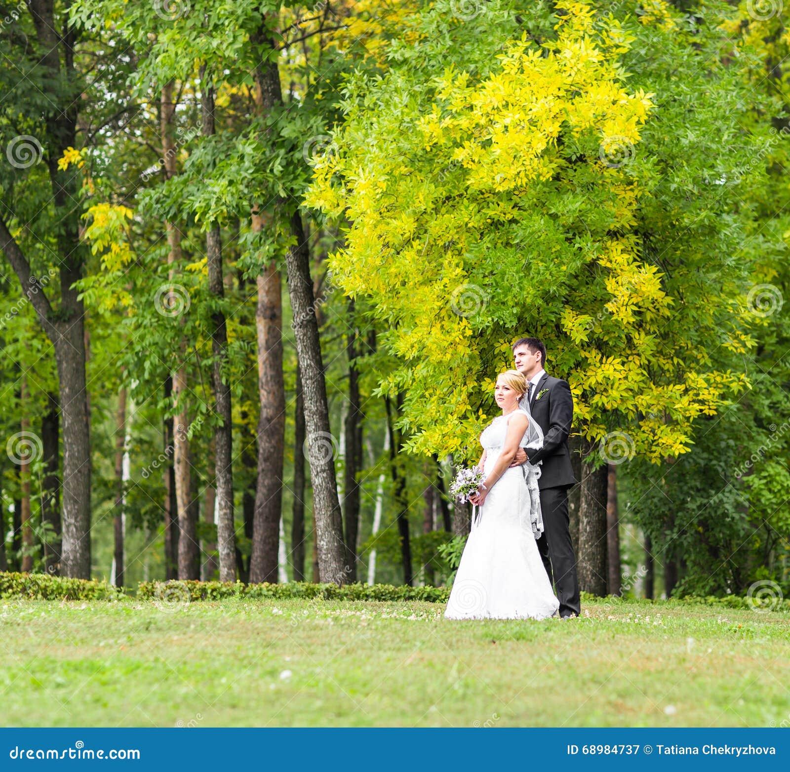 Pares românticos bonitos do casamento que beijam e que abraçam fora