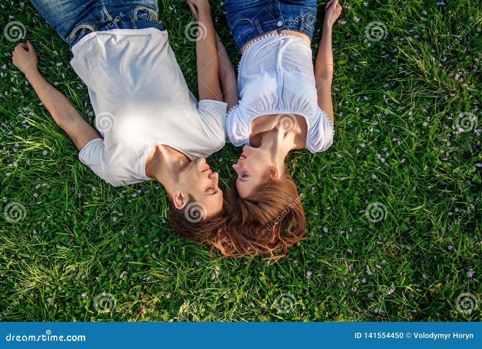 Pares românticos de jovens que encontram-se na grama no parque Colocam nos ombros de se e mantêm as mãos unidas