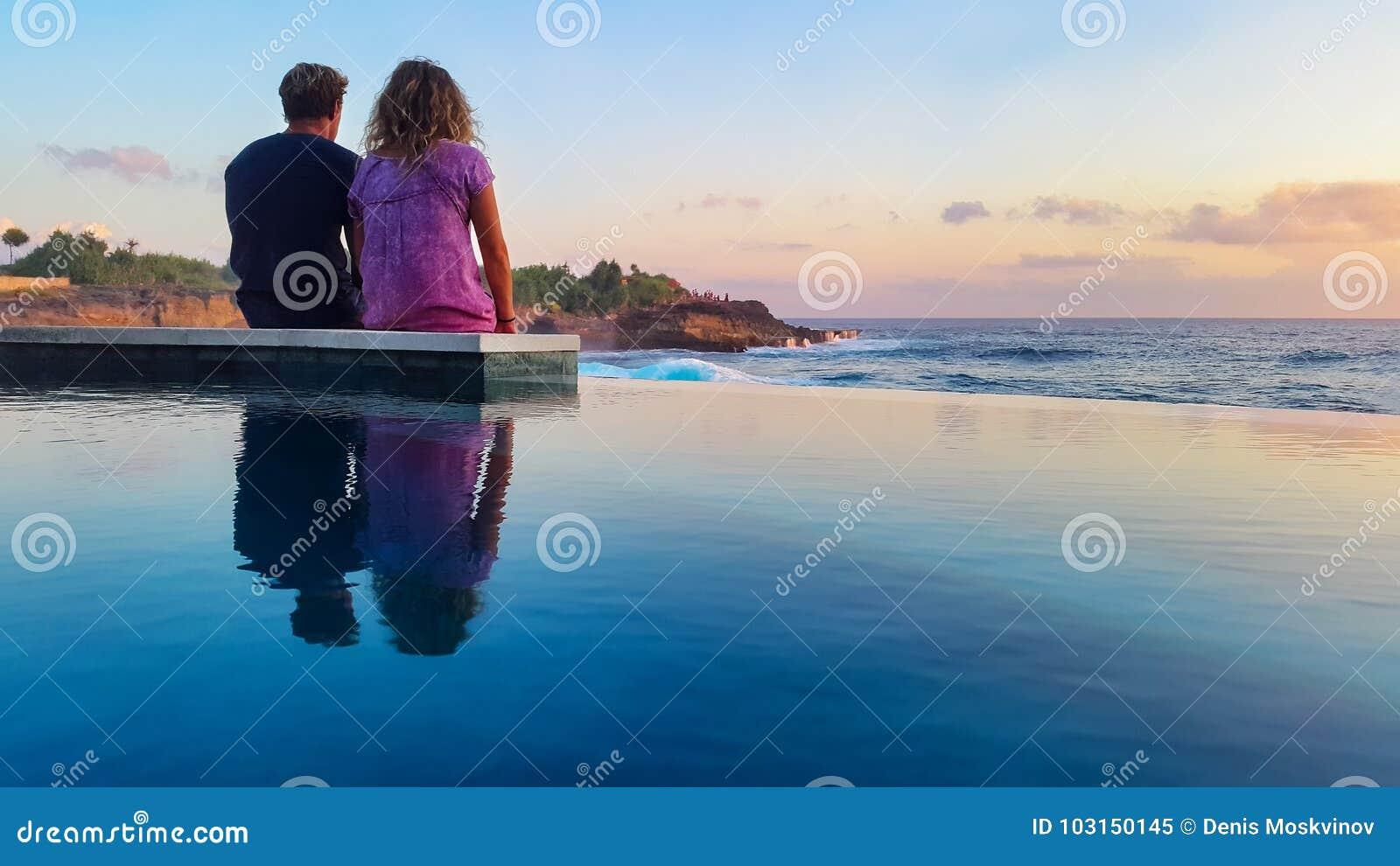Pares românticos na praia do por do sol