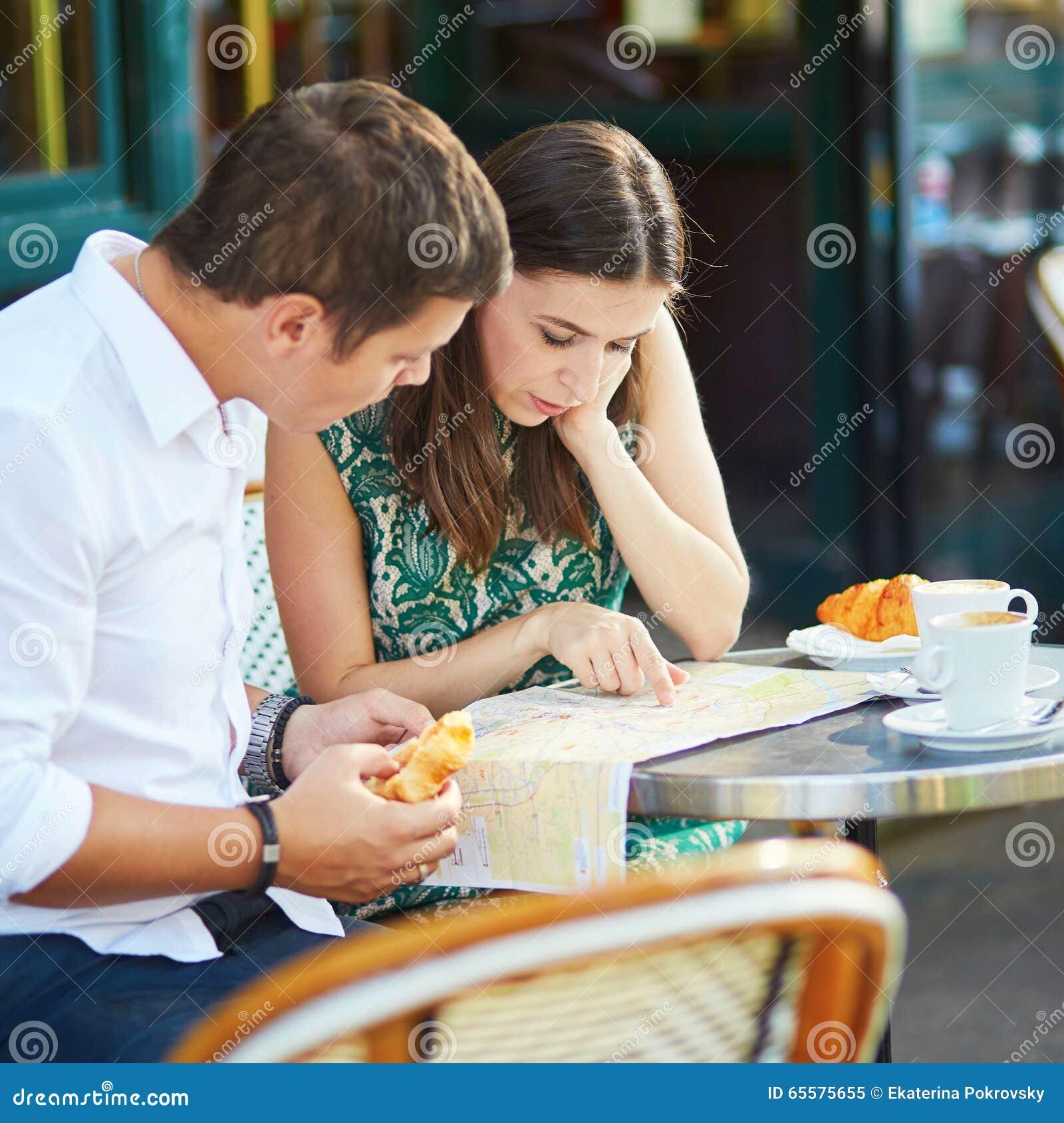 Pares românticos novos usando o mapa em um café exterior acolhedor em Paris, França