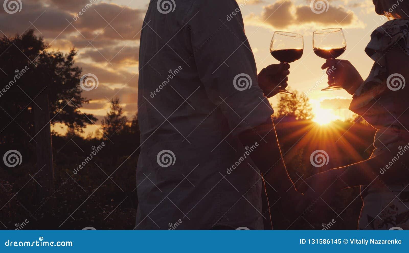 Pares românticos que guardam vidros do tim-tim das mãos com vinho no por do sol