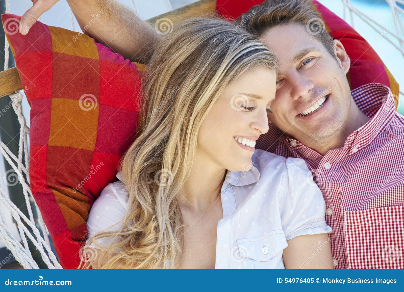 Pares românticos que relaxam na rede do jardim junto