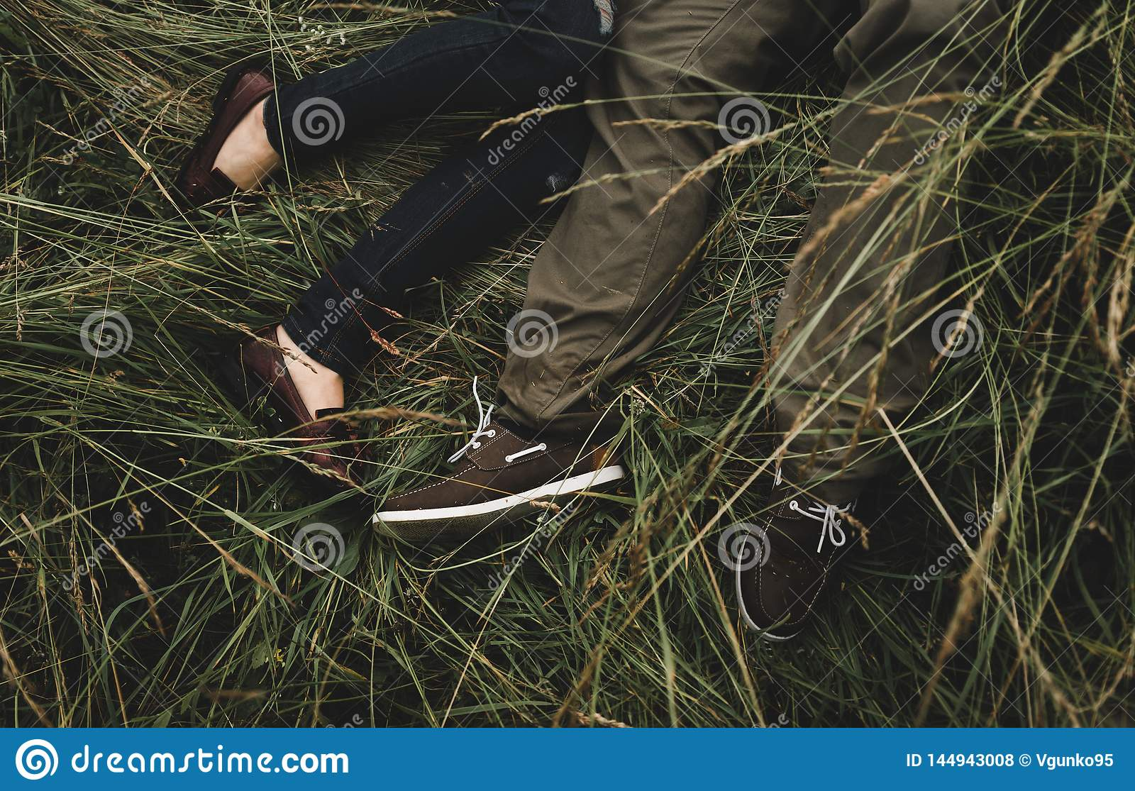 Pares rom?nticos de la gente joven que miente en hierba en parque