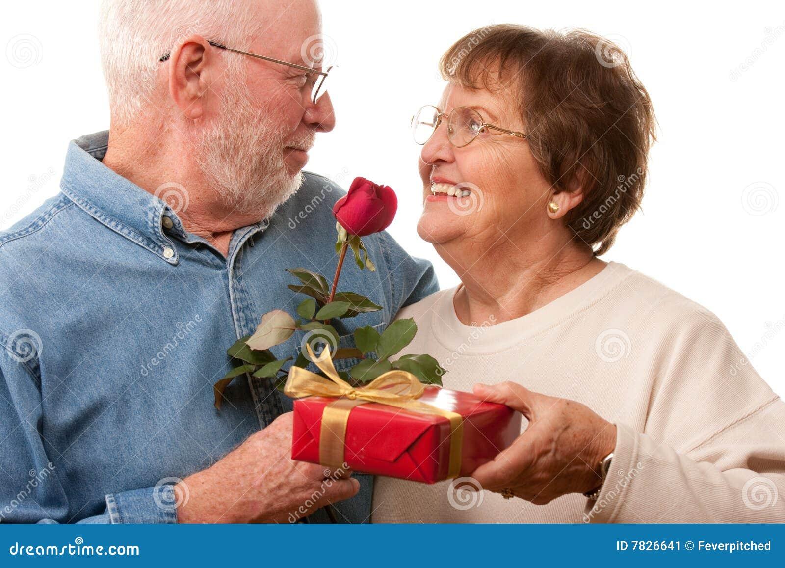 Pares sênior felizes com presente e a Rosa vermelha