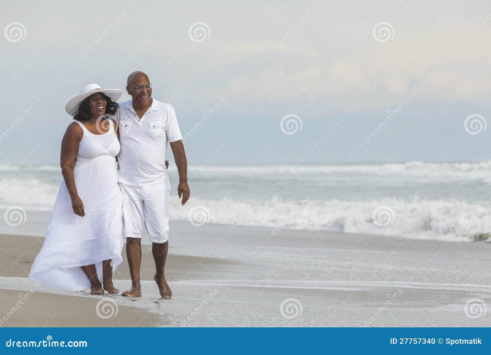 Pares sênior felizes do americano africano na praia