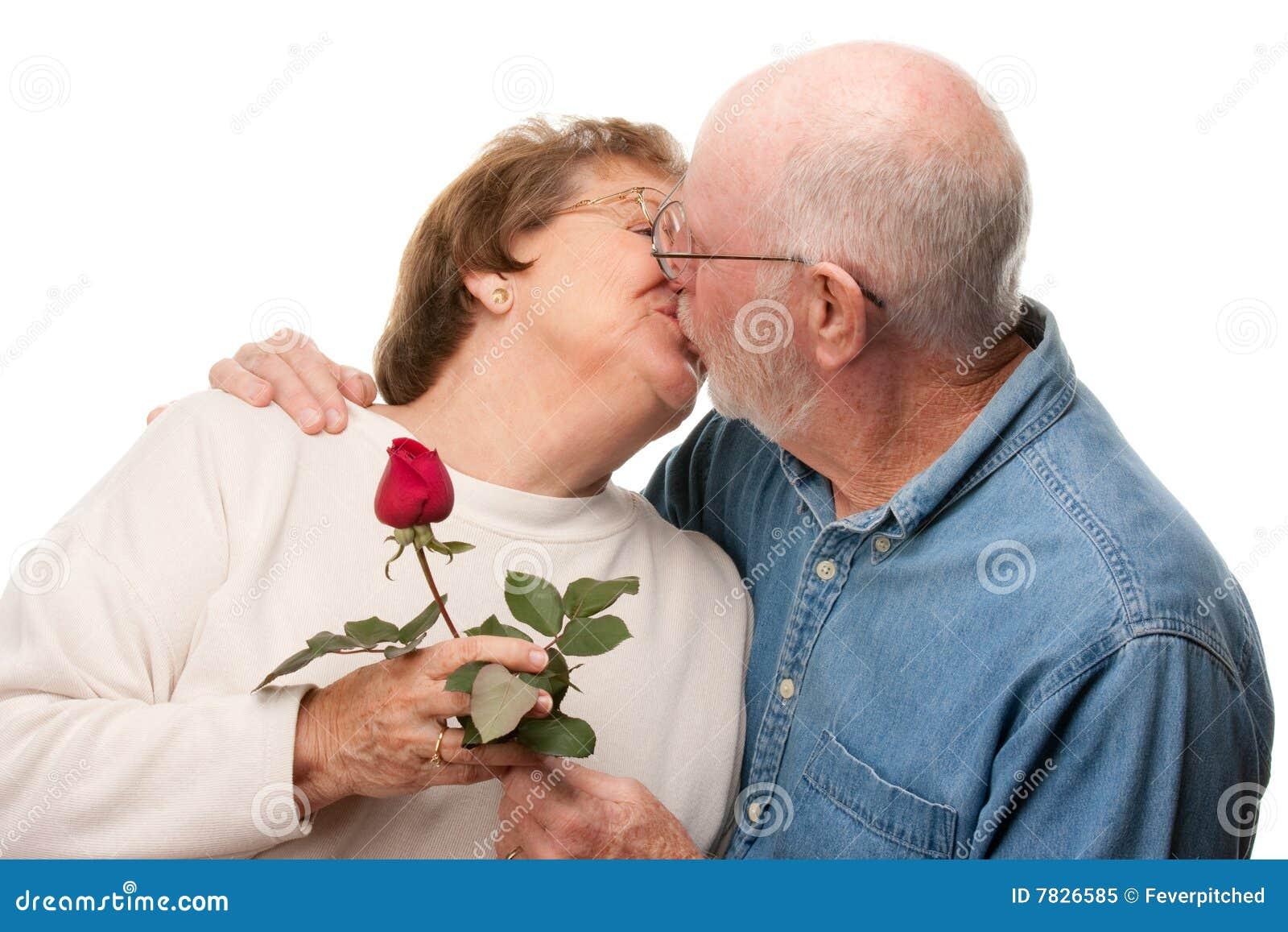 Pares sênior felizes que beijam com Rosa vermelha