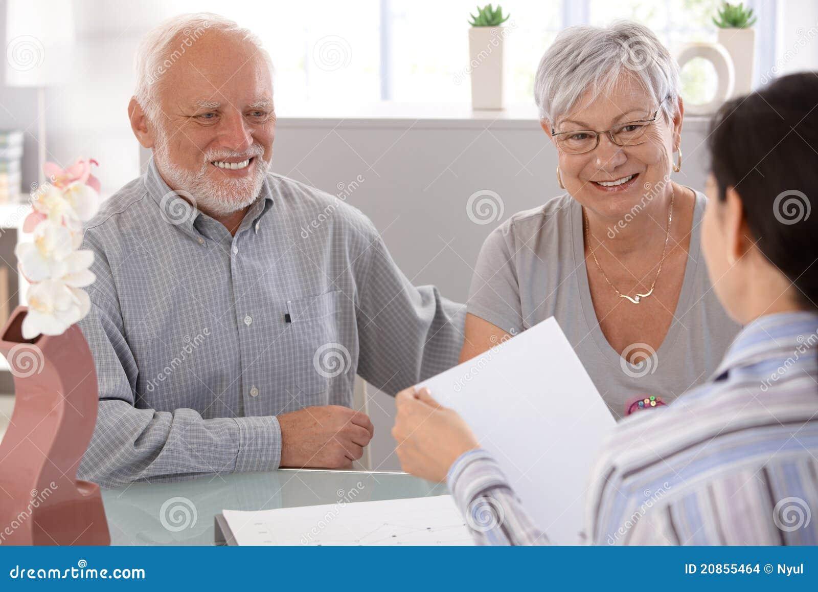 Pares sênior no sorriso financeiro do conselheiro