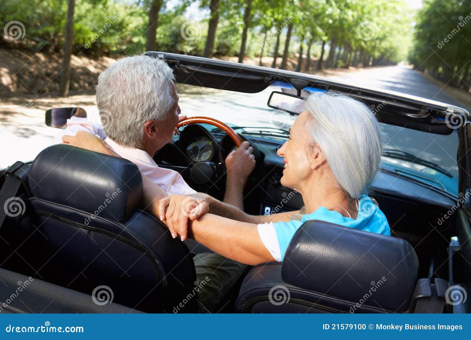 Pares sênior que conduzem no carro de esportes