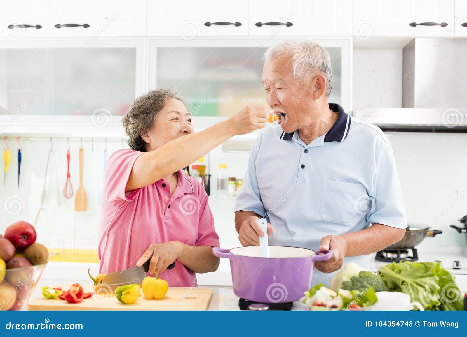 Pares sênior que cozinham na cozinha