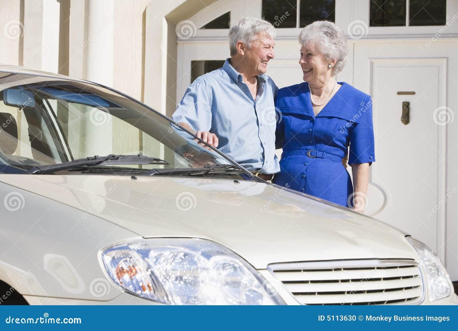 Pares sênior que estão ao lado do carro