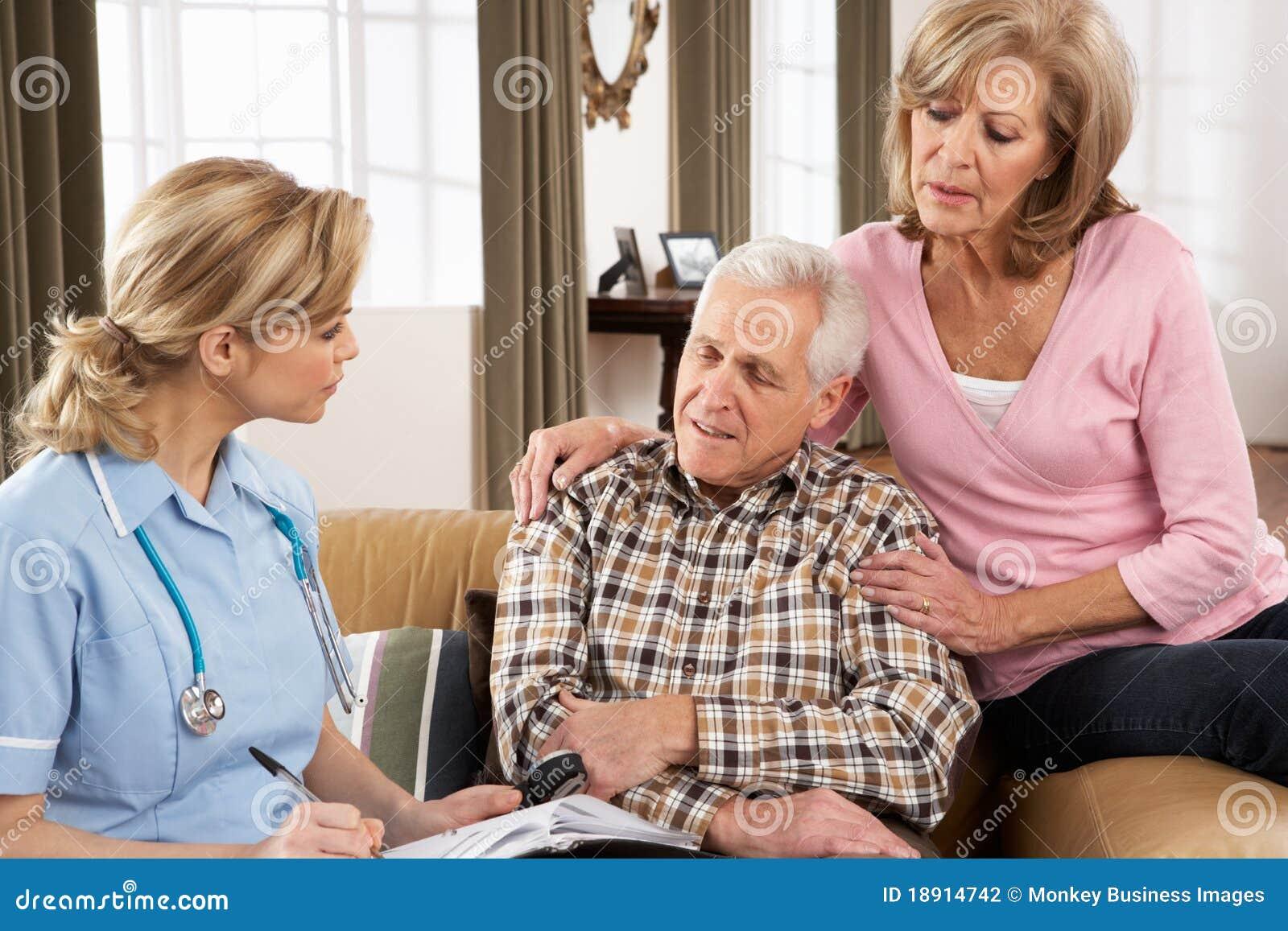 Pares sênior que falam ao visitante da saúde