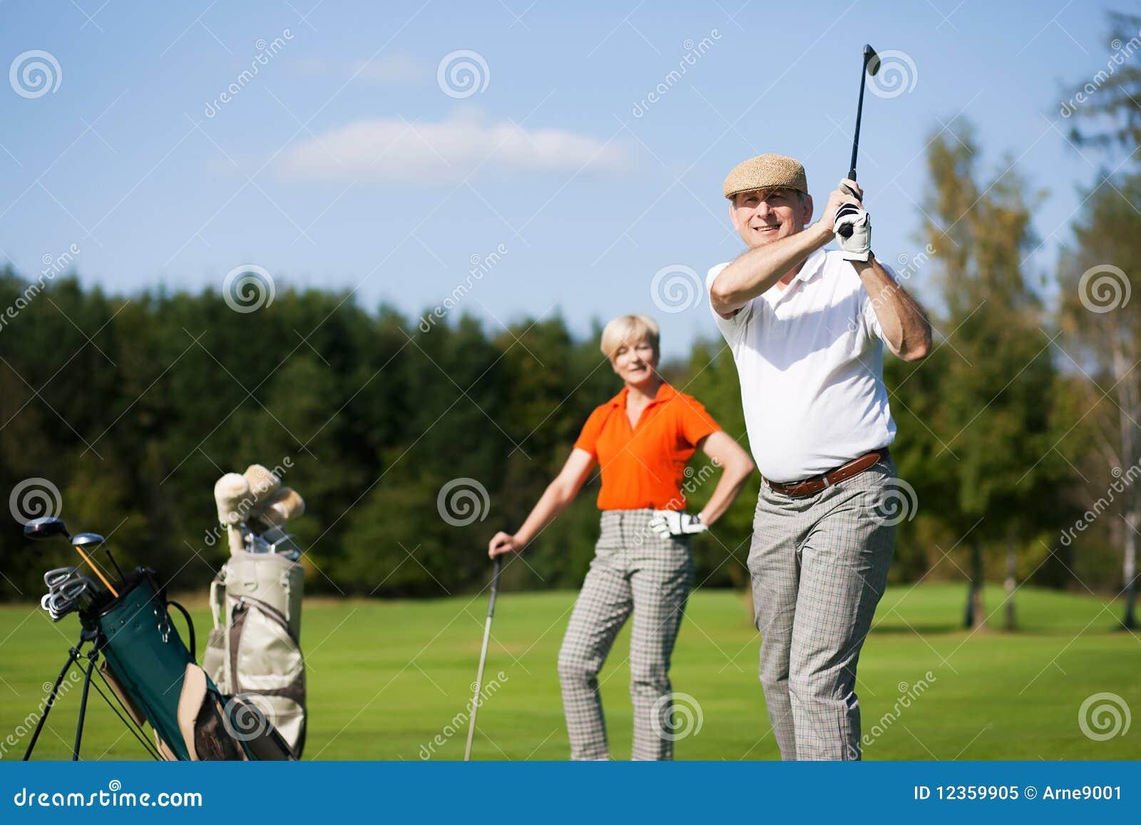 Pares sênior que jogam o golfe