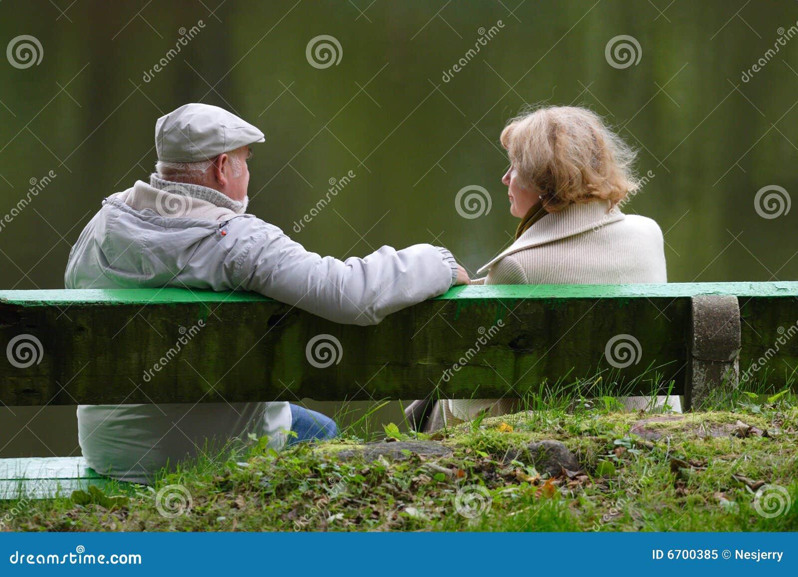 Pares sênior que sentam-se em um banco