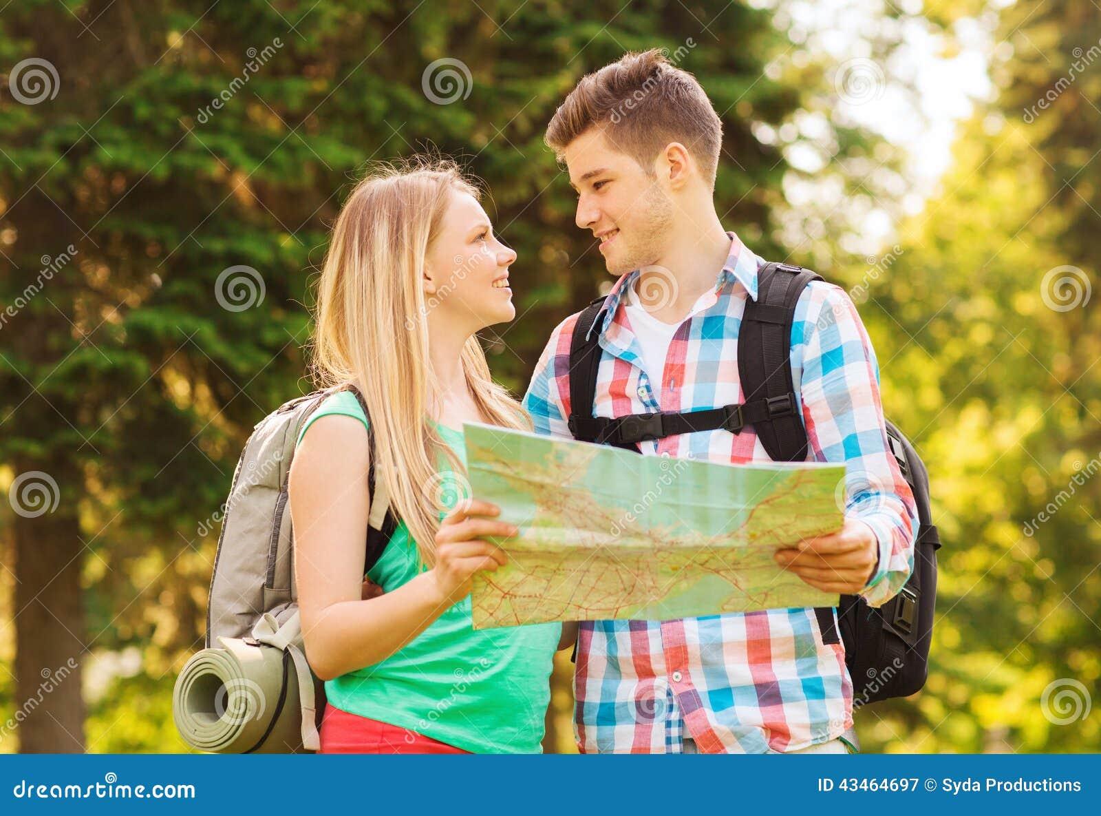 Pares sonrientes con el mapa y mochilas en bosque