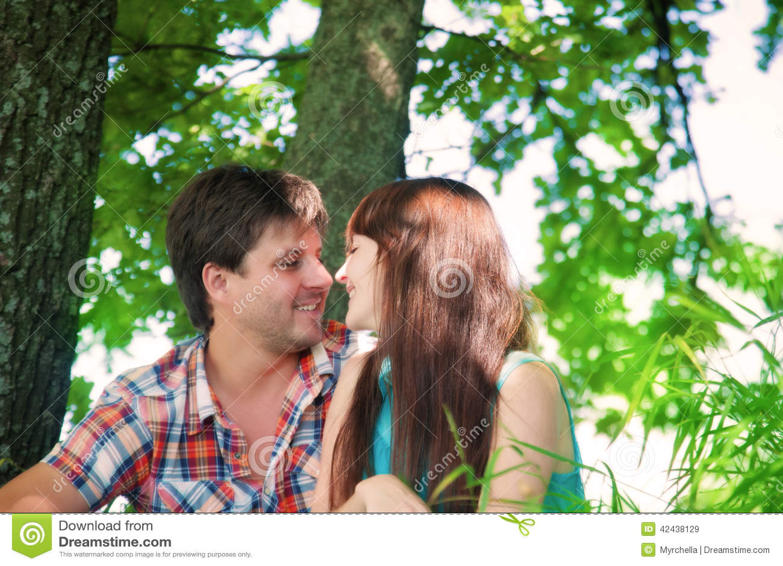 Pares sonrientes que descansan cerca de un árbol