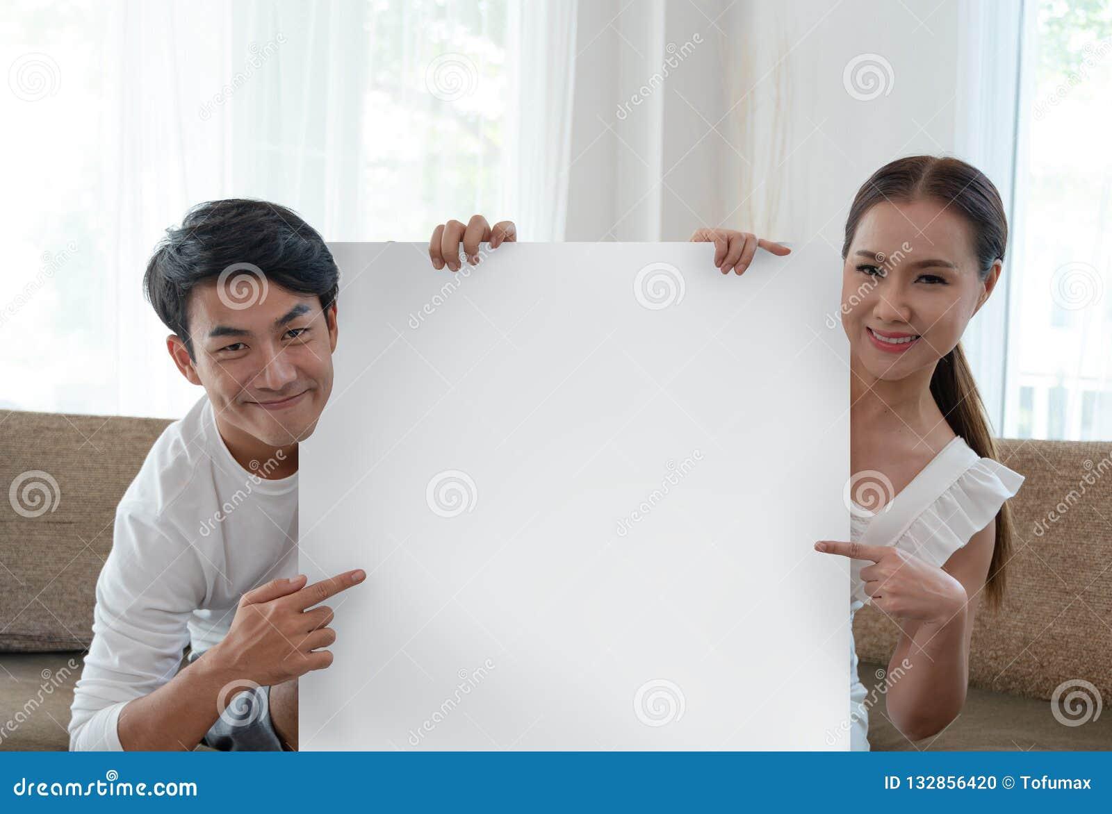 Pares sonrientes que sostienen la cartulina blanca en blanco