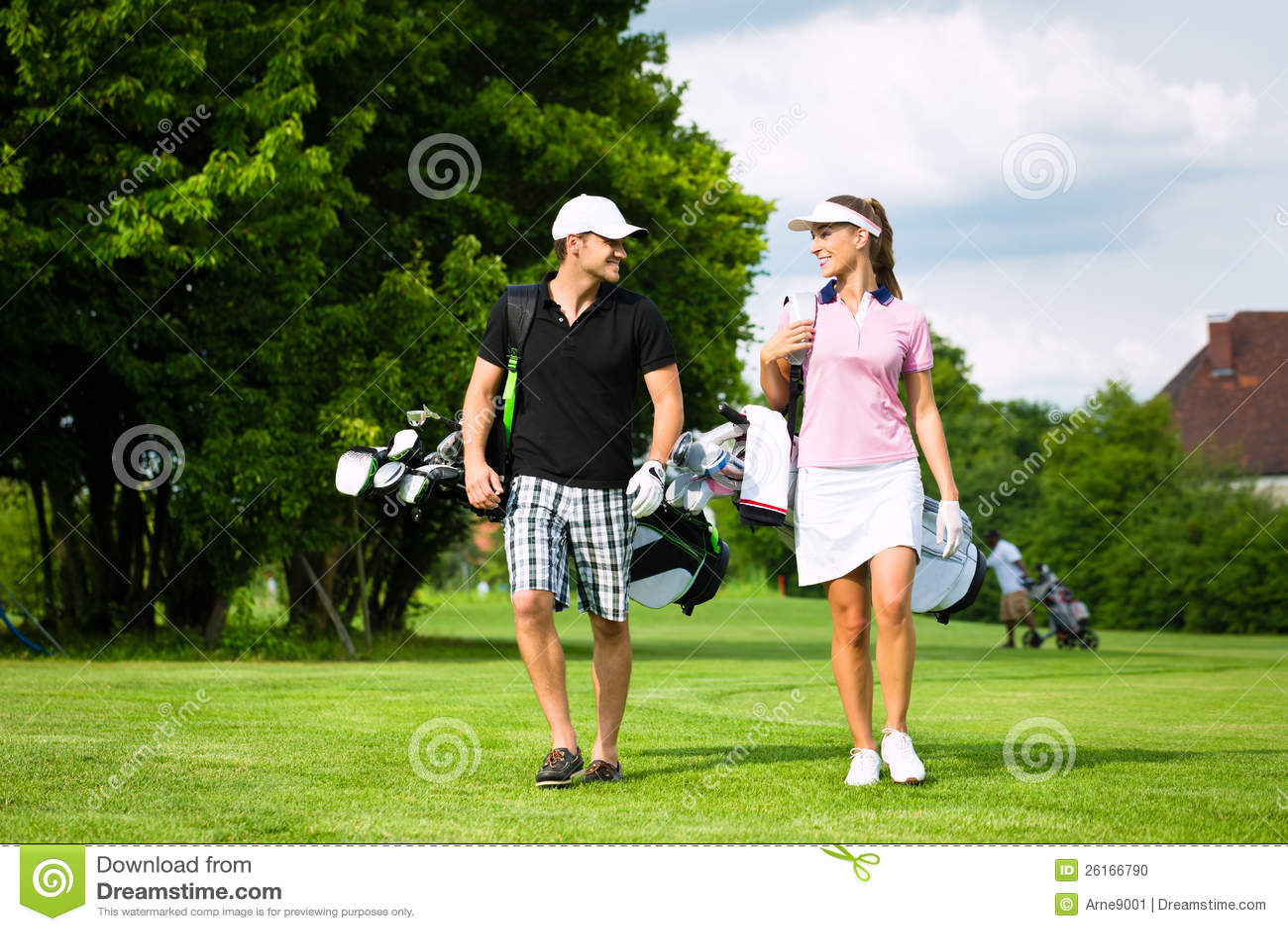 Pares sportive novos que jogam o golfe em um curso