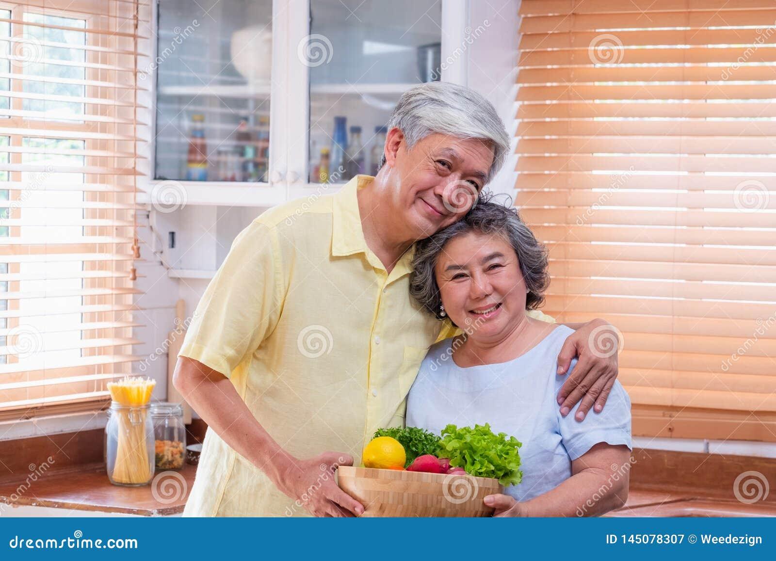 Pares superiores asiáticos da felicidade do retrato na cozinha com uma bacia de salada fresca e vista da câmera, envelhecendo e
