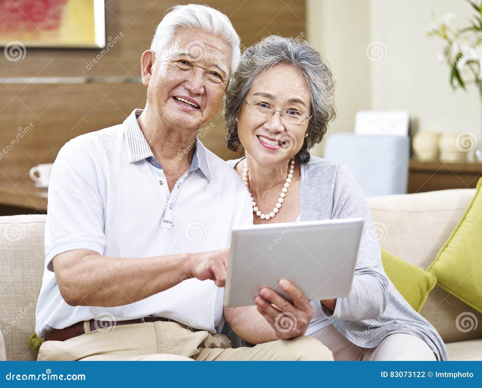 Pares superiores asiáticos felizes usando a tabuleta