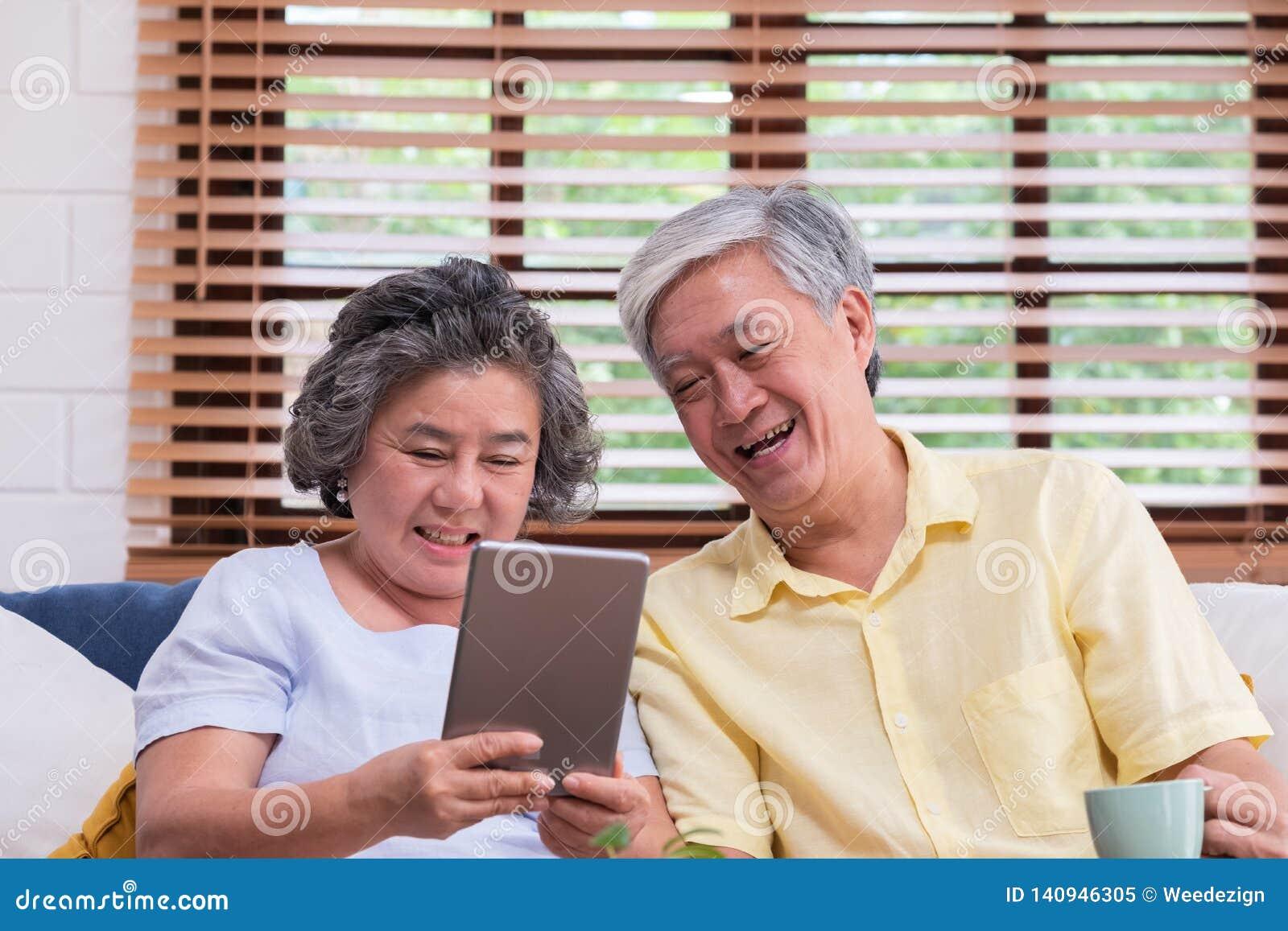 Pares superiores asiáticos para aprender a usar o cálculo da tabela no sofá na sala de visitas em casa superior com lfiestyle da