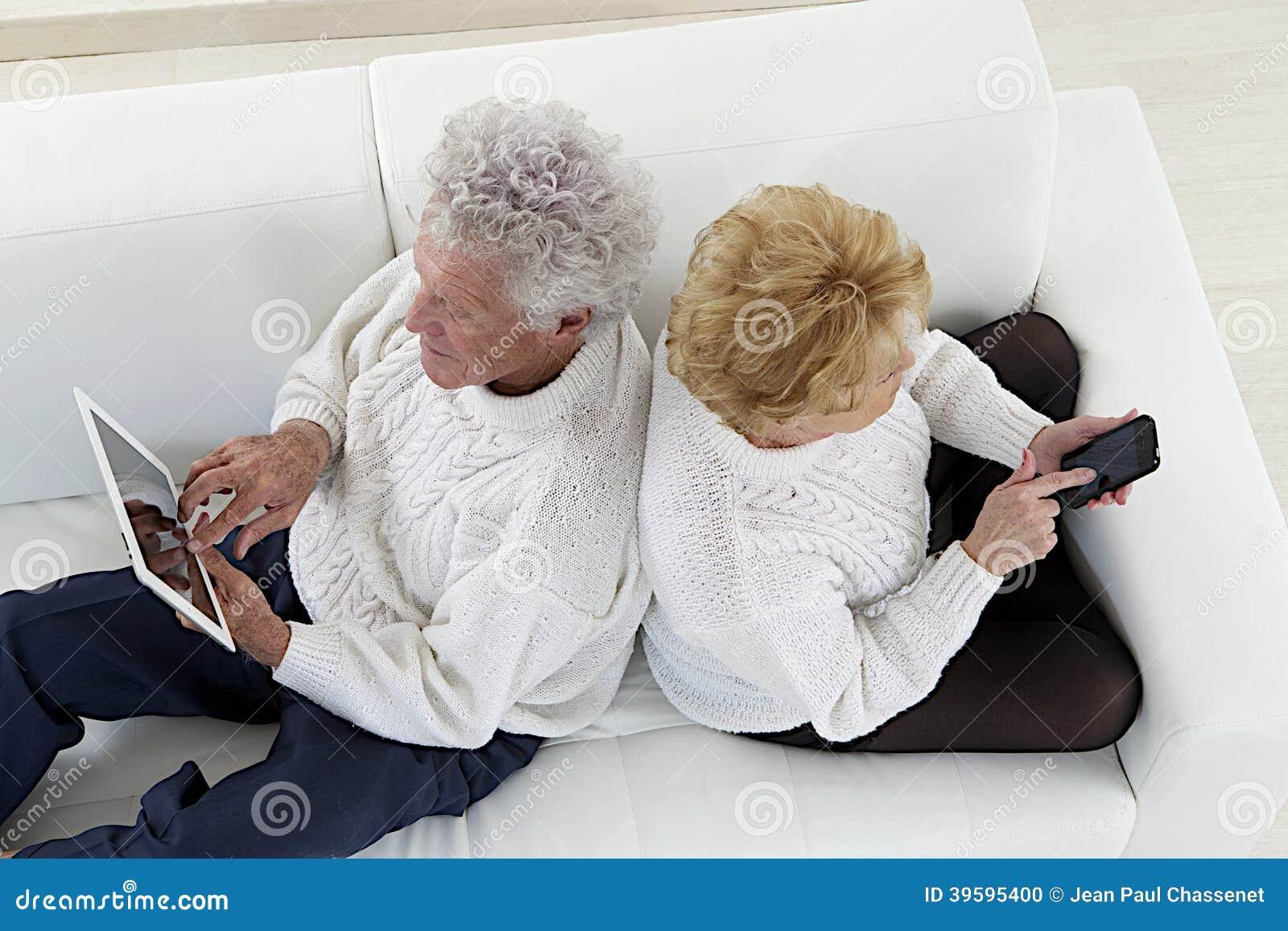 Pares superiores assentados de volta ao jogo traseiro com tabuletas e iphones