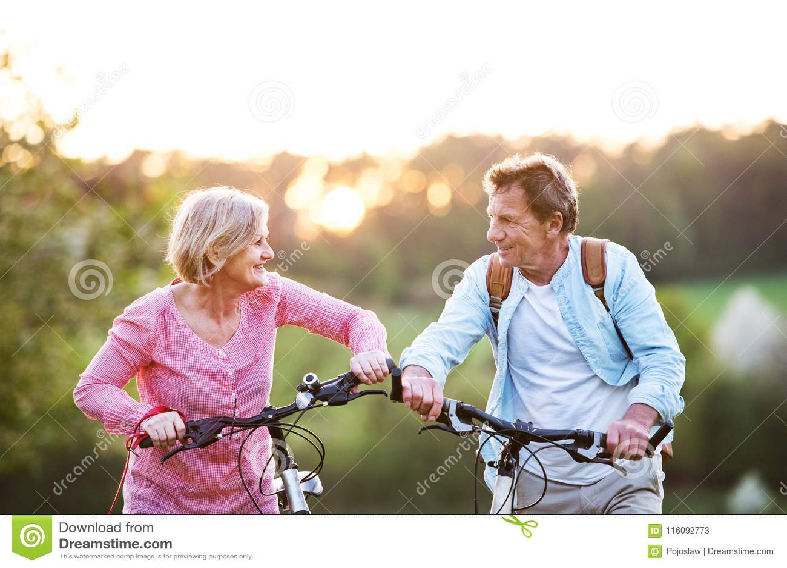 Pares superiores bonitos com bicicletas fora na natureza da mola