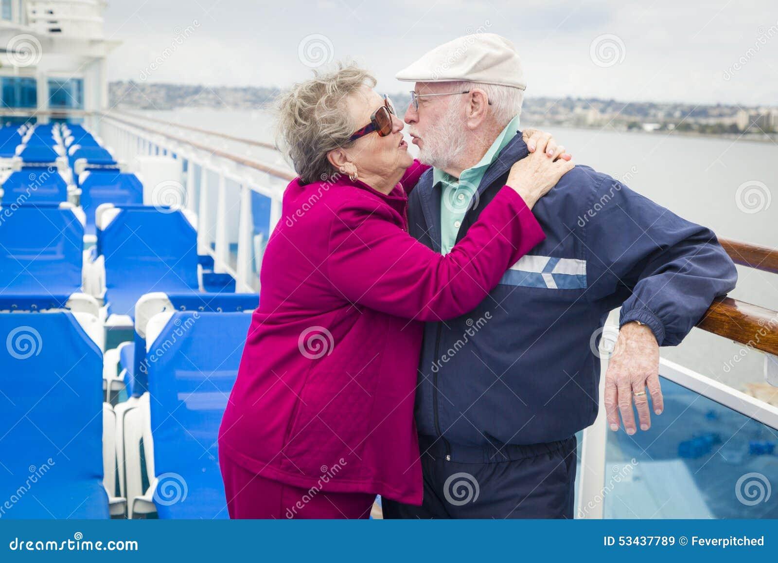 Pares superiores doces que beijam na plataforma do navio de cruzeiros